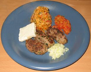 Cavapcici mit Djuvecreis, Ajvar, Schafskäse und frischen Zwiebeln